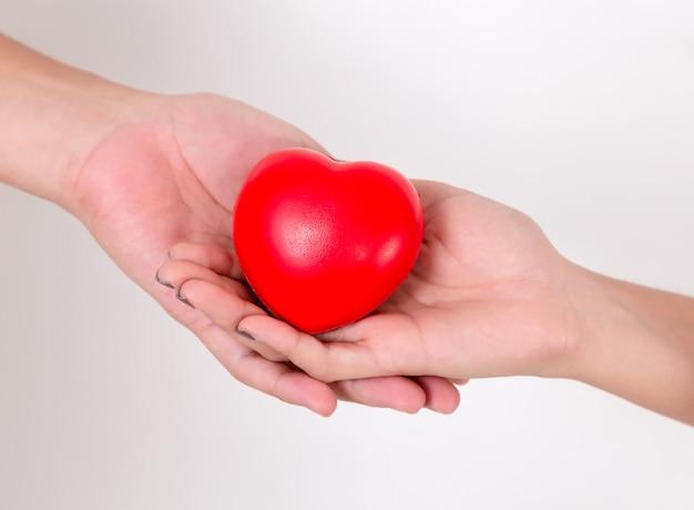 Coeur dans les mains de l'amour de couple.