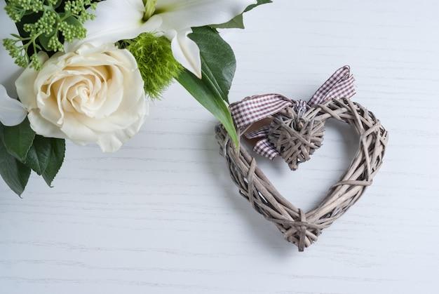 Cœur décoratif et fleurs aromatiques roses blanches sur fond en bois peint blanc.