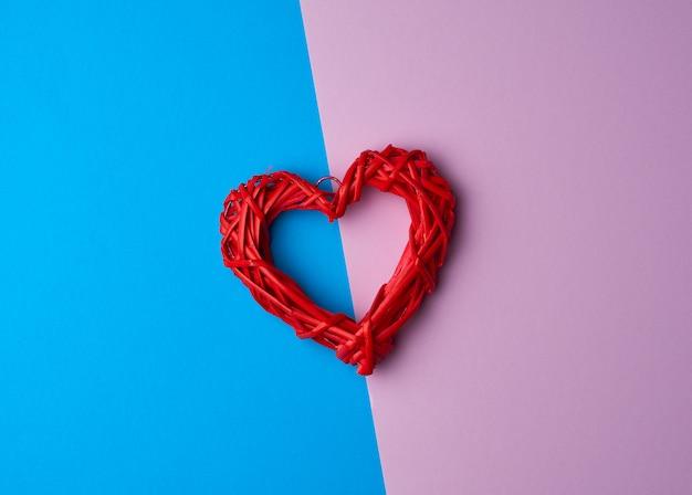 Coeur décoratif en osier rouge sur une surface lilas bleu