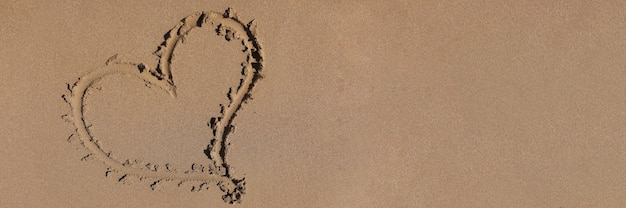 Coeur dessiné sur le sable par fond de mer gros plan