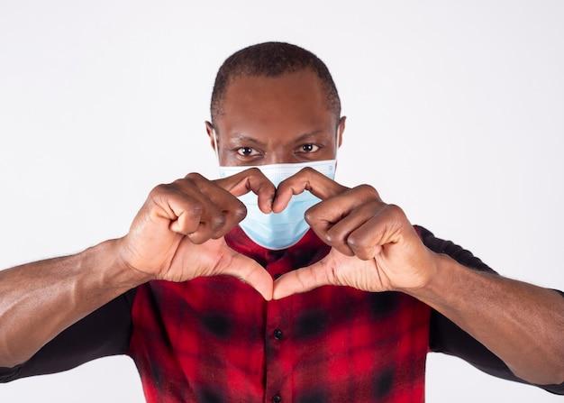 Coeur avec les doigts, covid-19, homme afro avec masque