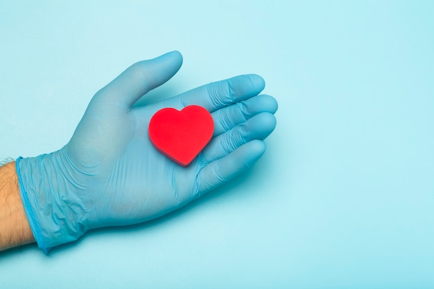 Coeur entre les mains d'un médecin sur un fond de bannière coloré don de charité traitement de santé aide...