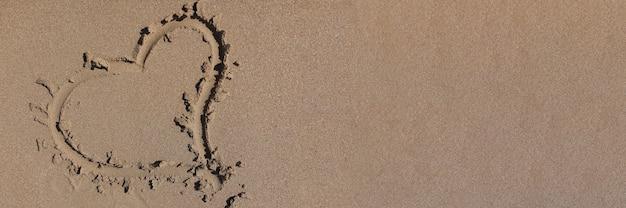 Le cœur est dessiné sur le sable humide sur la plage