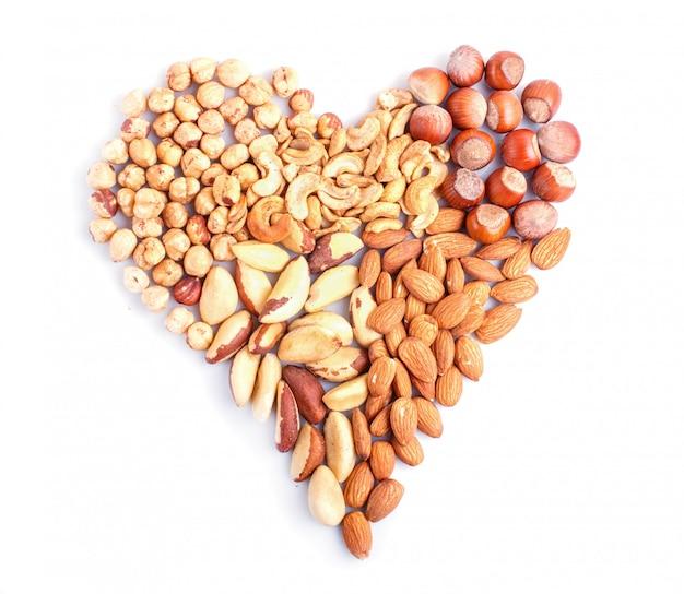 Cœur fabriqué à partir de différents types de noix isolé sur blanc