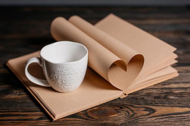 Coeur fabriqué à partir de feuilles de livre avec une tasse, l'amour et le concept de la saint-valentin sur une table en bois