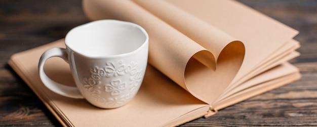 Coeur fait de feuilles de livre avec un concept de tasse, d'amour et de saint-valentin sur une table en bois