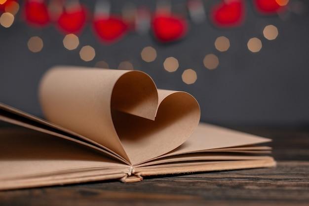 Coeur fait de feuilles de livre dans les lumières, l'amour et le concept de la saint-valentin sur une table en bois