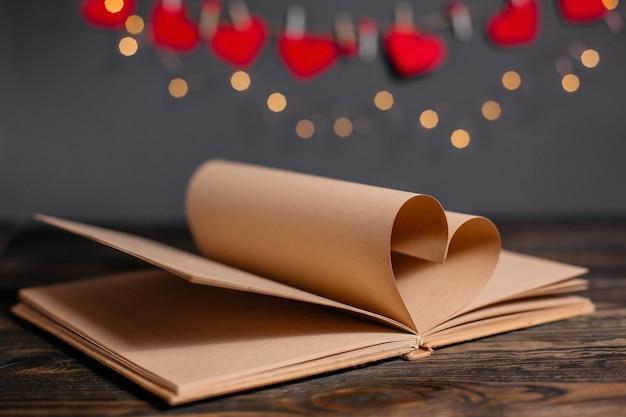 Coeur fait de feuilles de livre en lumières, amour et concept de la saint-valentin sur une table en bois