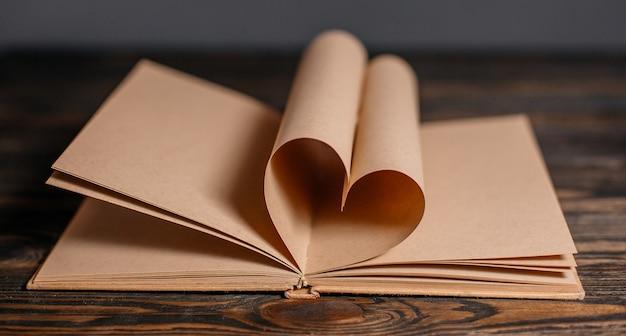 Coeur fait de feuilles de livre sur une table en bois