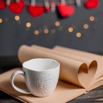 Coeur fait de feuilles de livre avec une tasse dans les lumières, l'amour et le concept de la saint-valentin sur une table en bois