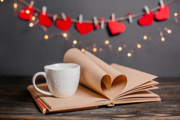 Coeur fait de feuilles de livre avec une tasse dans les lumières, l'amour et la saint-valentin concept sur une table en bois