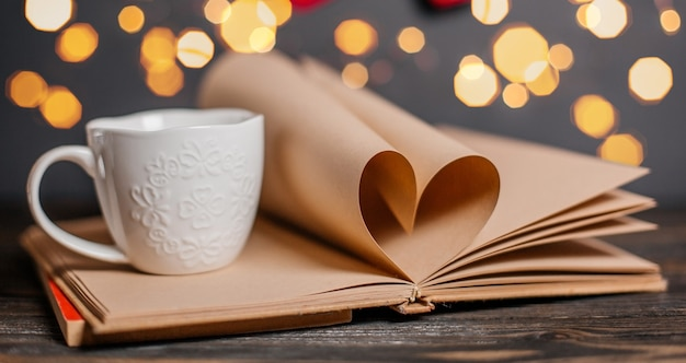 Coeur fait de feuilles de livre avec une tasse dans les lumières