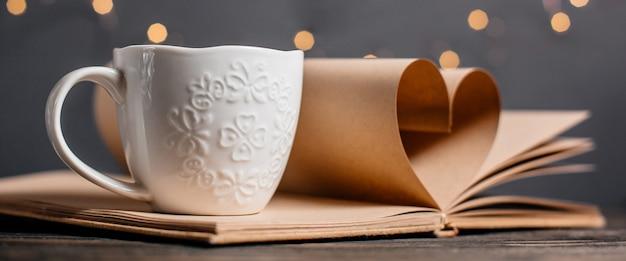 Coeur fait de feuilles de livre avec une tasse en lumières, amour et concept de la saint-valentin sur une table en bois