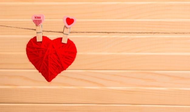 Un cœur fait de fil suspendu avec des pinces à linge