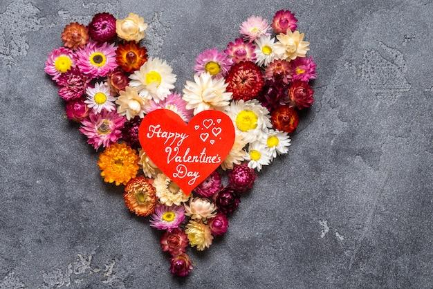 Coeur fait de fleurs sur fond gris