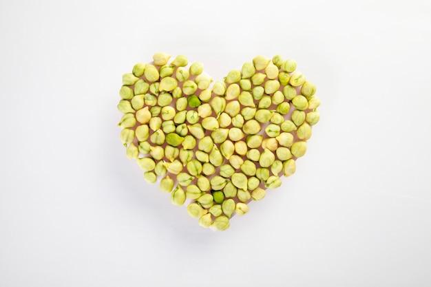 Coeur fait de légumineuses de pois chiches fraîches sur mur blanc, concept de vie et de nutrition saine