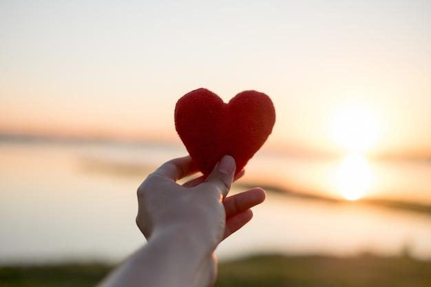Le coeur fait avec la main et le soleil est la toile de fond.
