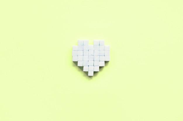 Un coeur fait de morceaux de sucre repose sur un citron vert pastel à la mode
