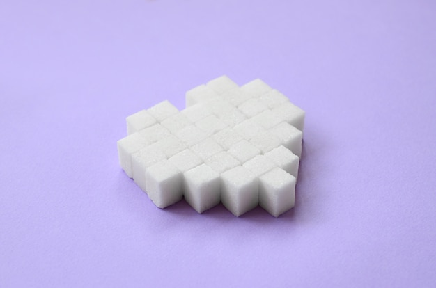 Un coeur fait de morceaux de sucre repose sur un fond violet pastel branché