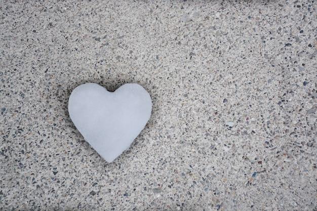 Un coeur fait de neige sur fond gris avec ombre