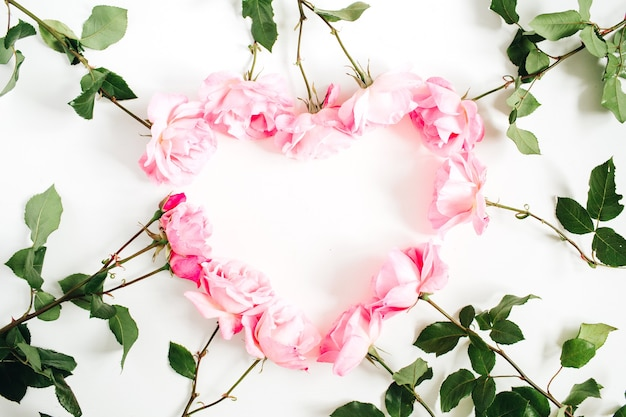 Coeur fait de roses roses sur blanc