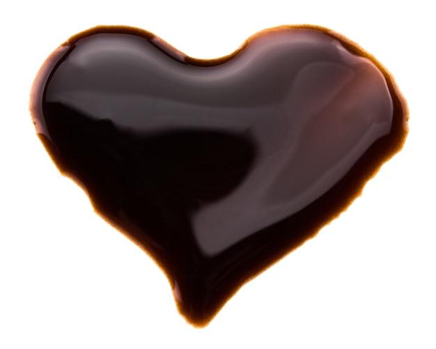 Coeur fait de sirop de chocolat, isolé sur blanc.