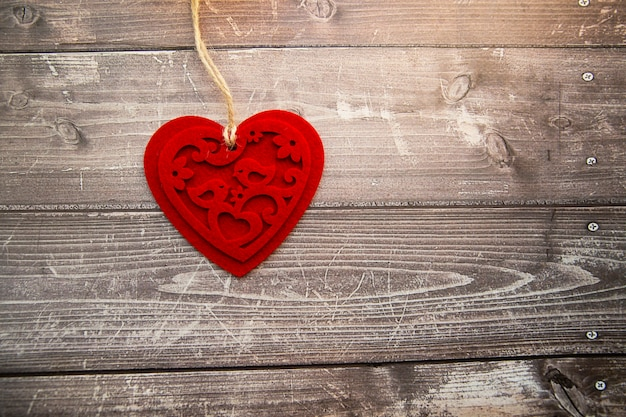 Coeur en feutre rouge sur un fond en bois. la saint-valentin