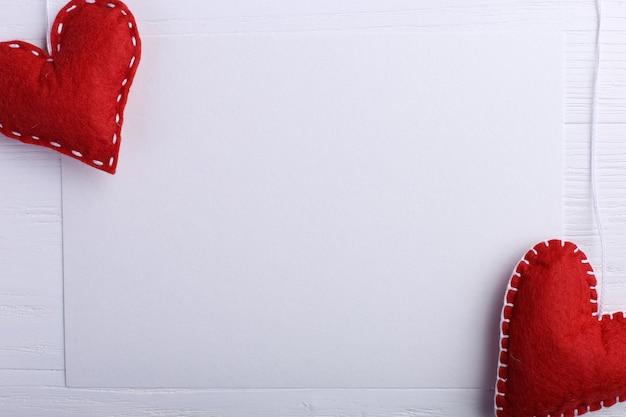 Coeur de feutre rouge à la main à côté de papier blanc sur une table en bois