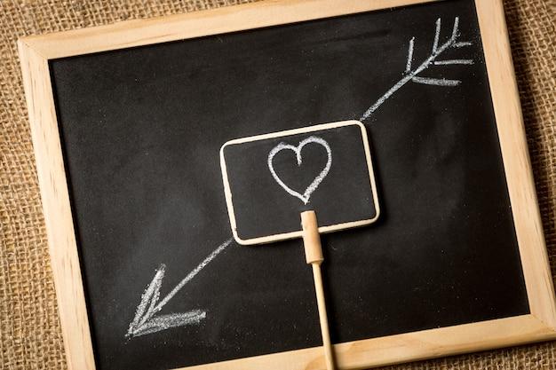 Coeur avec flèche dessinée à la craie sur tableau noir