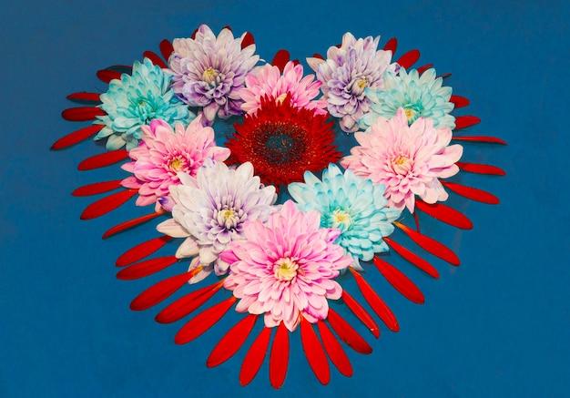 Un coeur de fleurs et de pétales sur fond bleu. la saint-valentin