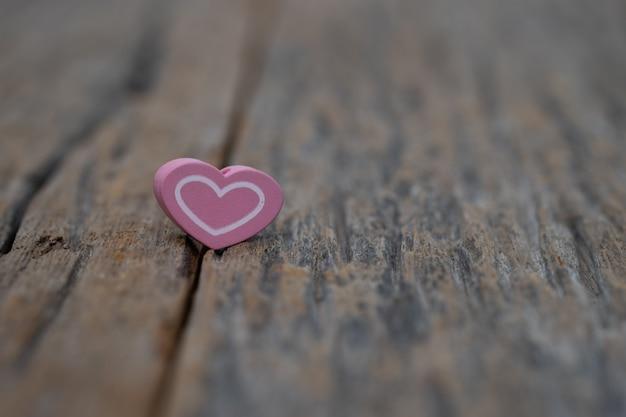 Un coeur sur fond en bois. espace copie saint-valentin.