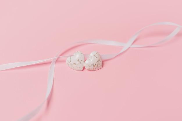 Coeur de forme avec ruban wihte sur fond rose isolé
