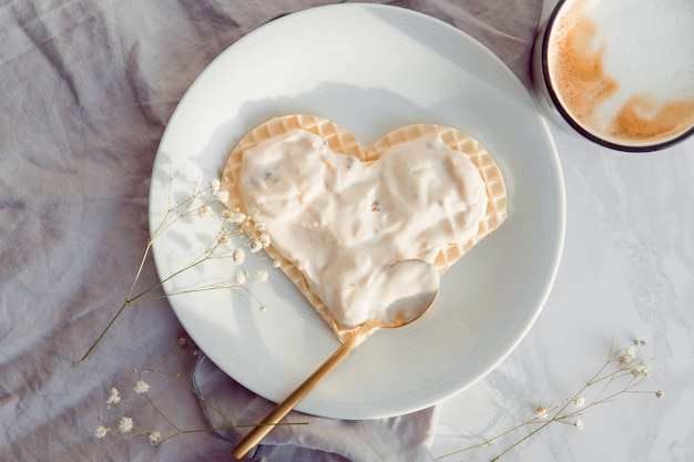 Coeur de gaufres pour le petit-déjeuner de la saint-valentin avec yogourt et café chaud