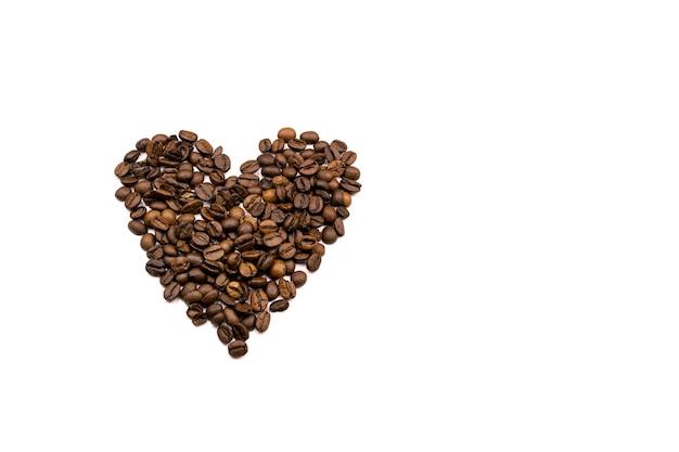 Coeur en grains de café sur fond blanc, vue de dessus, flatlay. la saint-valentin.