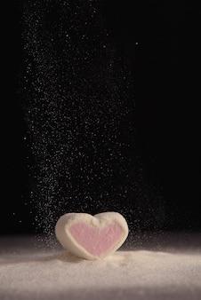 Coeur de guimauves sur fond noir en sucre en poudre.