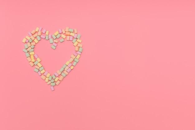 Cœur de guimauves multicolores isolé sur fond rose. amour, concept de félicitation.