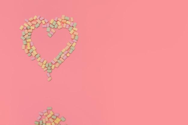 Cœur de guimauves multicolores isolé sur fond rose