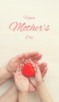 Coeur heureux de jour de mères dans les mains de la fille et de la mère sur le fond blanc