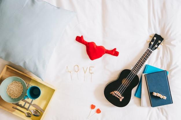 Coeur de jouet et d'amour écrivant près d'ukulélé