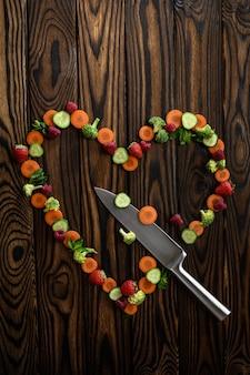 Coeur de légumes avec couteau sur fond en bois, vue de dessus. nourriture végétarienne biologique, assortiment d'épicerie, produits écologiques naturels, concept de mode de vie sain