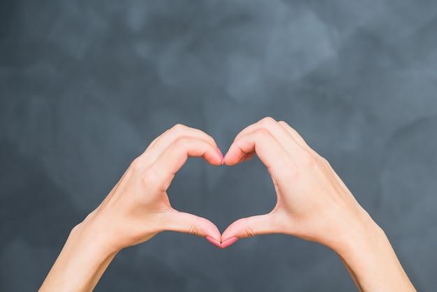 Cœur des mains féminines sur fond gris. amour, thème de la relation.