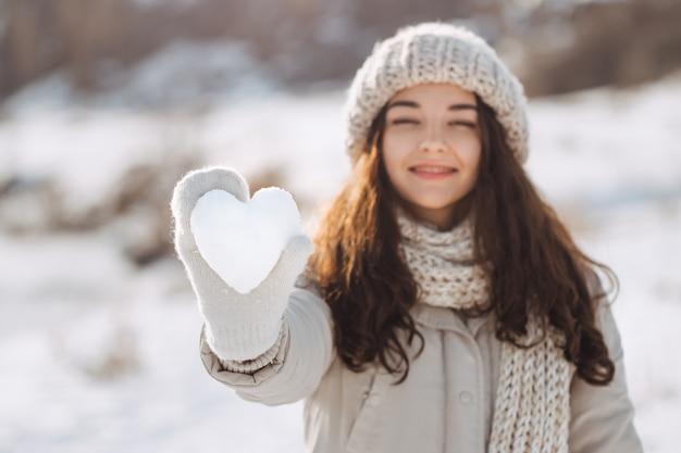 Coeur de neige dans la main de la femme à l'extérieur