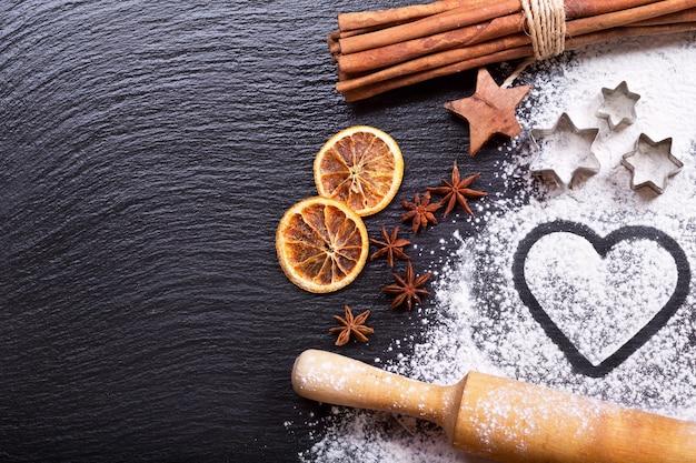 Coeur de noël à base de farine et de fruits secs, bâtons de cannelle et étoiles d'anis