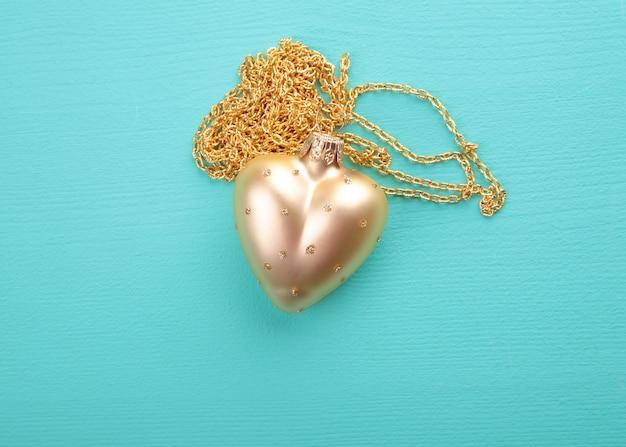 Coeur en or avec chaîne en or sur la texture du bois