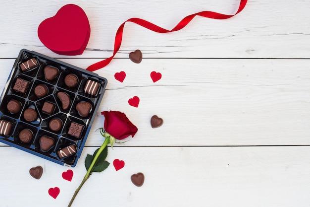 Coeur d'ornement près de ruban, fleur et bonbons