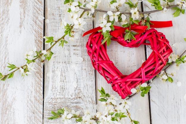 Un coeur en osier rouge et des branches de cerisier en fleurs