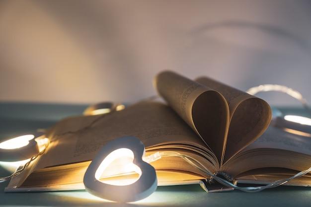 Coeur de pages de livre. style vintage avec bokeh dans une lumière douce la nuit, flou, espace de copie, concept pour la saint-valentin.
