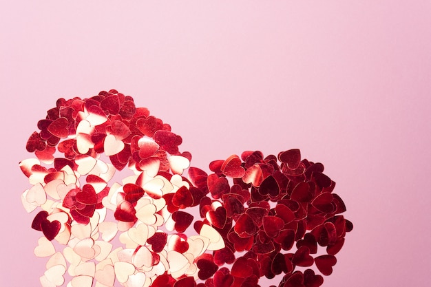 Coeur de paillettes rouges sur rose