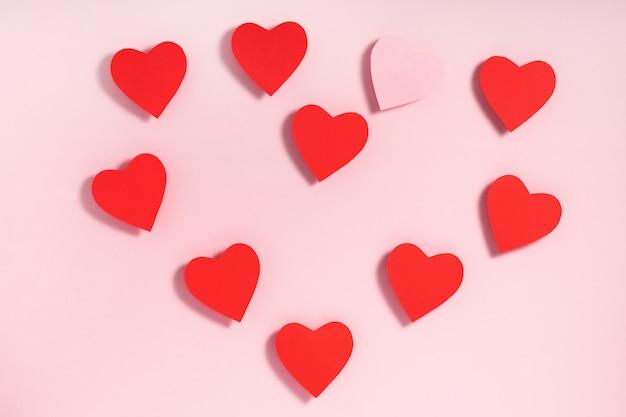 Coeur en papier coeurs rouges et roses sur fond rose