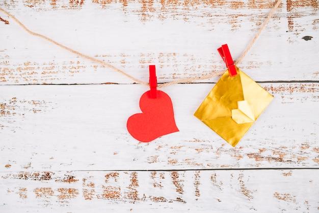 Cœur en papier et enveloppe avec épingles accrochées au fil